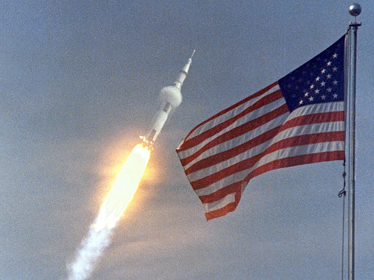 The American flag heralds the flight of Apollo 11, the first Lunar landing mission. The Apollo 11 Saturn V space vehicle lifted off with astronauts Neil A. Armstrong, Michael Collins and Edwin E. Aldrin, Jr., at 9:32 a.m. EDT July 16, 1969, from Kennedy Space Center's Launch Complex 39A. During the planned eight-day mission, Armstrong and Aldrin will descend in a lunar module to the Moon's surface while Collins orbits overhead in the Command Module. The two astronauts are to spend 22 hours on the Moon, including two and one-half hours outside the lunar module. They will gather samples of lunar material and will deploy scientific experiments which will transmit data about the lunar environment. They will rejoin Collins in the Command Module for the return trip to Earth.