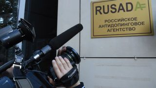 A journalist films the sign on the RUSADA (Russia's anti-doping agency) building in Moscow on September 20, 2018. - The World Anti-Doping Agency (WADA) on September 20, 2018 lifted a ban on Russia's anti-doping agency (RUSADA), paving the way for Russian athletes to return to competition across all sports. (Photo by Kirill KUDRYAVTSEV / AFP)