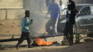 """Locals set tyres on fire and block a sidestreet leading to their neighbourhood in the Sudanese capital Khartoum to stop military vehicles from driving through the area on June 4, 2019. - Sudan's protest movement called the same day for fresh rallies and rejected the military rulers' election plan after more than 35 people were killed in what demonstrators called a """"bloody massacre"""" by security forces. (Photo by - / AFP)"""