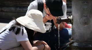 Tourists drink from a public fountain to refresh themselves during an unusually early summer heatwave on June 24, 2019 in Rome. - Fans flew off store shelves and public fountains offered relief from the heat as temperatures soared in Europe on June 24, with officials urging vigilance ahead of even hotter conditions forecast later in the week. Meteorologists blamed a blast of torrid air from the Sahara for the unusually early summer heatwave, which could send thermometers up to 40 degrees Celsius (104 Fahrenheit) across large swathes of the continent. (Photo by Alberto PIZZOLI / AFP)