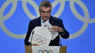 International Olympic Committee (IOC) president Thomas Bach prepares to show the card with the winning name which will host the 2026 Winter Olympics during the 134th session of the International Olympic Committee (IOC), in Lausanne on June 24, 2019. (Photo by Fabrice COFFRINI / AFP)