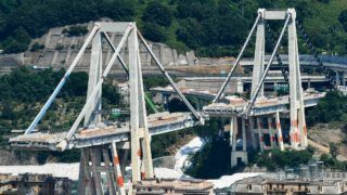 A general view shows the two pylons of Genoa's Morandi motorway bridge that are to be destroyed with explosives, seen in red on the concrete structure below, on June 27, 2019 in Genoa. - Some of the remains of Genoa's Morandi motorway bridge are set to be destroyed on June 28 almost eleven months after its partial collapse during a storm killed 43 people and injured dozens. (Photo by Vincenzo PINTO / AFP)