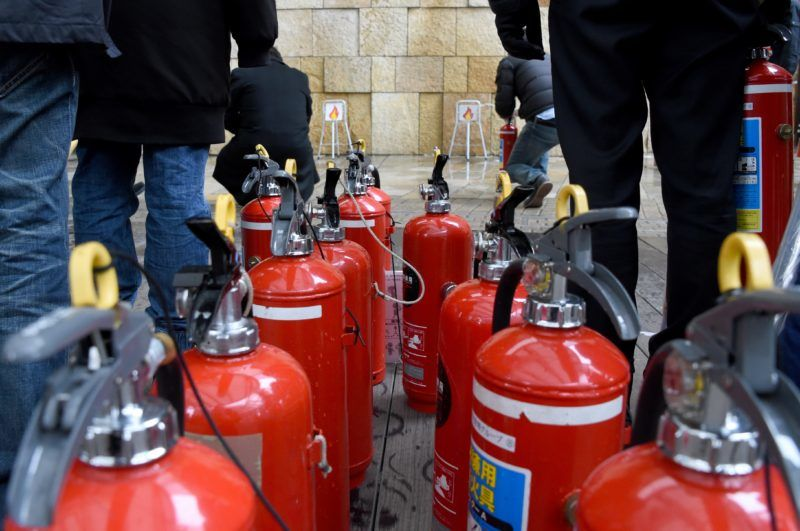 Residents take part in a lesson on how to use fire extinguishers during an earthquake drill at the Roppongi Hills shopping complex in Tokyo on March 11, 2016. - Some 900 citizens around the Roppingi Hills took part in the disaster drill on the fifth anniversary day of a terrifying 9.0-magnitude earthquake and tsunami that killed almost 19,000 people and sparked a nuclear disaster. (Photo by TOSHIFUMI KITAMURA / AFP)