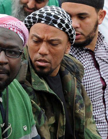 Picture taken on May 5, 2012 shows former German rapper Denis Cuspert (C) among salafi in Bonn, Germany. Denis Mamadou Cuspert, who rapped under the name Deso Dogg but took on the name Abu Talha al-Almani in Syria, was initially reported to have been killed in a suicide attack Sunday in an eastern province but hours later some retracted the claim, saying he was still alive. AFP PHOTO /DPA/  HENNING KAISER  GERMANY OUT (Photo by HENNING KAISER / DPA / AFP)