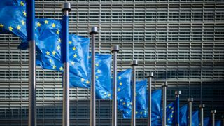 10 June 2019, Belgium, Brüssel: Flags of the European Union fly in the wind in front of the Berlaymont building, the seat of the European Commission. Photo: Arne Immanuel Bänsch/dpa