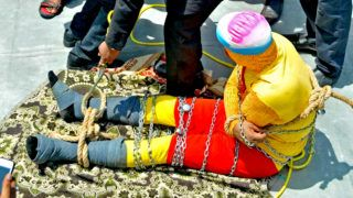 """In this photo taken on June 16, 2019 Indian stuntman Chanchal Lahiri, known by his stage name """"Jadugar Mandrake"""", is prepared for being lowered into the Ganges river, while tied up with steel chains and ropes, in Kolkata. - An Indian magician who went missing after being lowered into a river tied up in chains and ropes in a Houdini-inspired stunt is feared drowned, police said June 17. (Photo by STR / AFP)"""