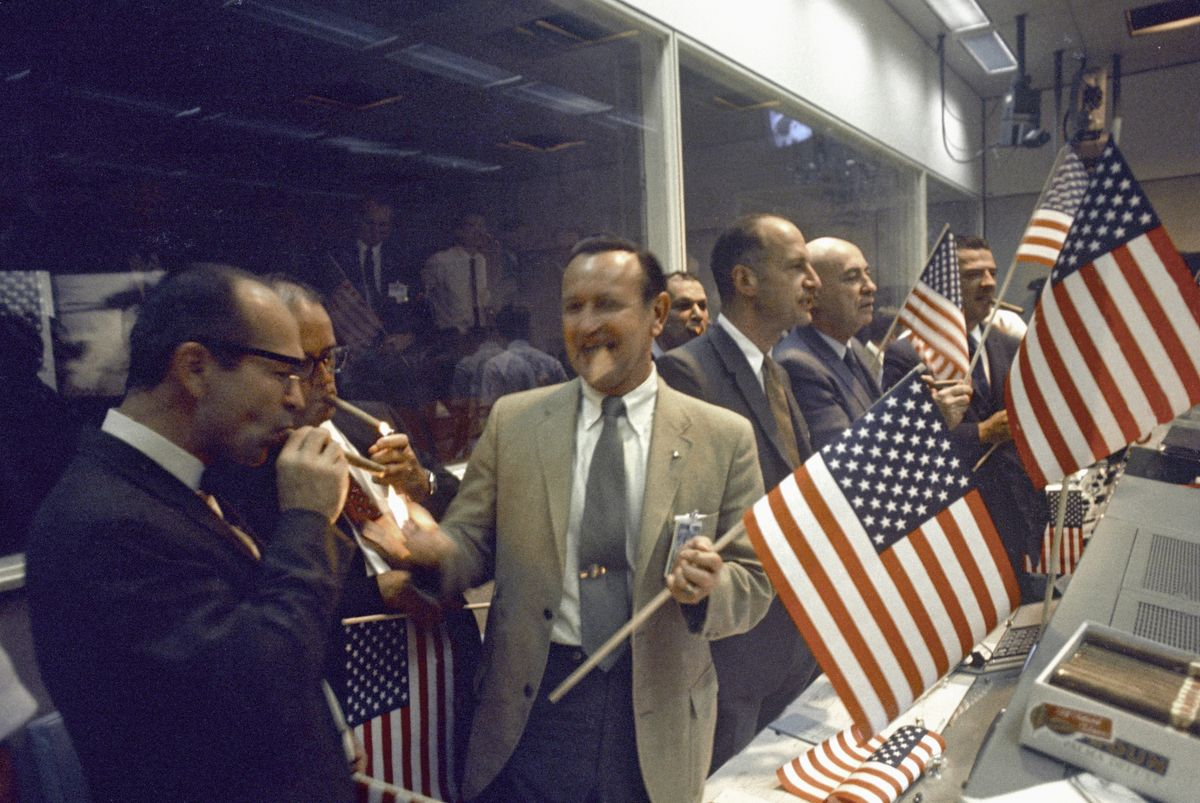 NASA and Manned Spacecraft Center (MSC) officials join the flight controllers in celebrating the conclusion of the Apollo 11 mission. From left foreground Dr. Maxime A. Faget, MSC Director of Engineering and Development; George S. Trimble, MSC Deputy Director; Dr. Christopher C. Kraft Jr., MSC Director fo Flight Operations; Julian Scheer (in back), Assistant Adminstrator, Office of Public Affairs, NASA HQ.; George M. Low, Manager, Apollo Spacecraft Program, MSC; Dr. Robert R. Gilruth, MSC Director; and Charles W. Mathews, Deputy Associate Administrator, Office of Manned Space Flight, NASA HQ. (Photo by VCG Wilson/Corbis via Getty Images)