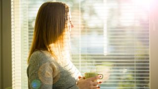 Woman standing at home by the window with cup of hot coffee wearing knitted warm sweater. Cozy sunny room filled with light. beautiful morning behind the big window.