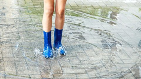 girl in blue rubber boots standing in a puddle after a rain outdoor on summer day. legs closeup
