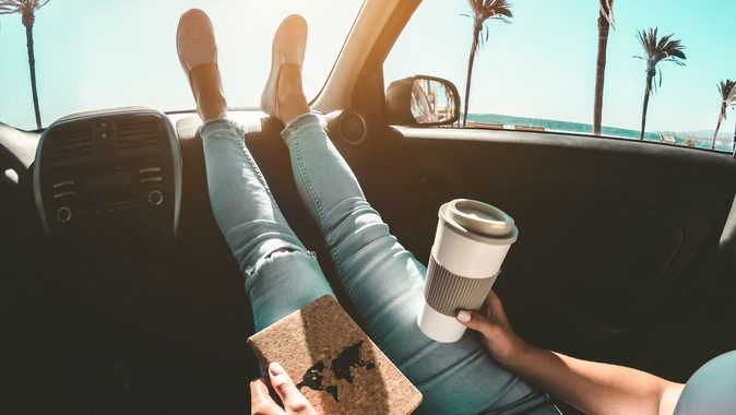 Woman drinking coffee paper cup inside car with feet on dashboard - Girl relaxing in auto trip reading travel book with ocean beach and palms in background - Traveler concept - Focus on hands