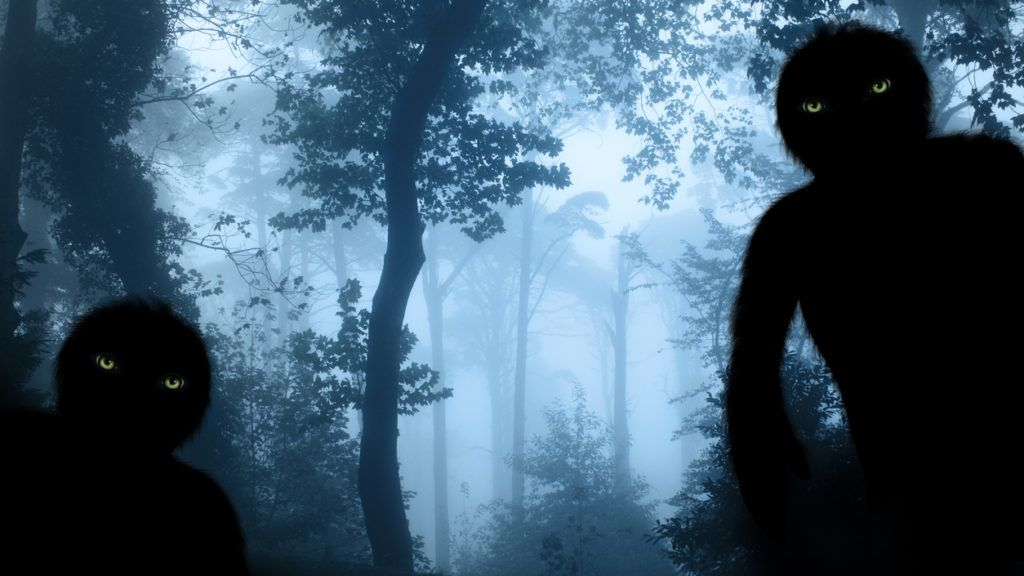 Two monsters with green eyes in misty forest landscape. Photo toned in blue color