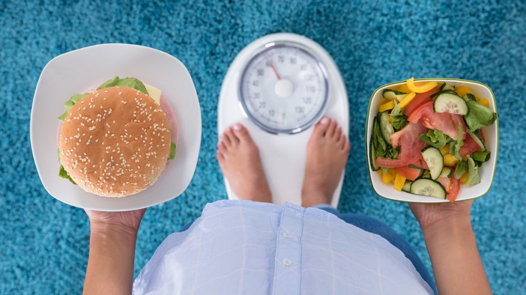 High Angle View Of A Person Holding Burger And Salad Standing On Weighing Machine