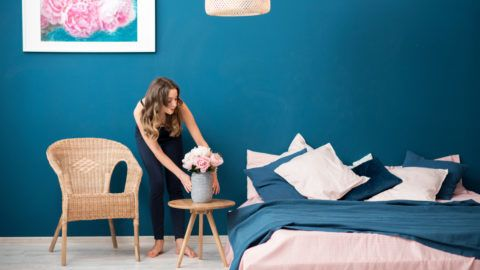 Young woman decorating bedroom with beautiful flowers at home