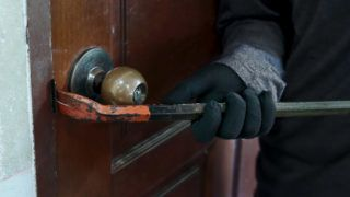 Hands of Masked thief with balaclava using crowbar to breaking into a house at night time. Crime concept.