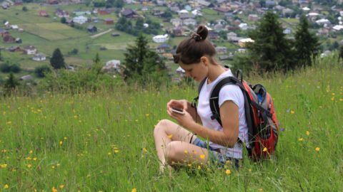 A girl tourist on the hill of the village with phone in hands