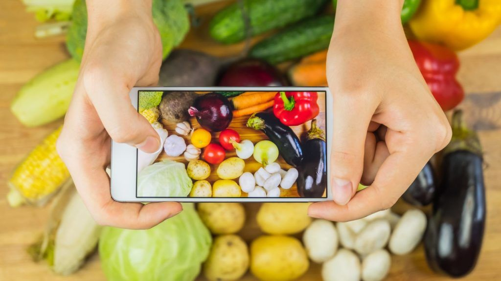 Close-up of female hands photographing flat lay of locally grown natural vegan food