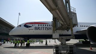 Pakistani airport ground staff gather around the British Airways aircraft after landing at the Islamabad International Airport, on the outskirts of Islamabad on June 3, 2019. - British Airways landed back in Pakistan Monday, in a major vote of confidence from a Western airline after suspending operations due to security fears over a decade ago. The British carrier -- which halted services in 2008 following the deadly Marriott Hotel bombing in Islamabad -- is running three weekly flights from London's Heathrow airport to Pakistan's capital, Islamabad. (Photo by AAMIR QURESHI / AFP)