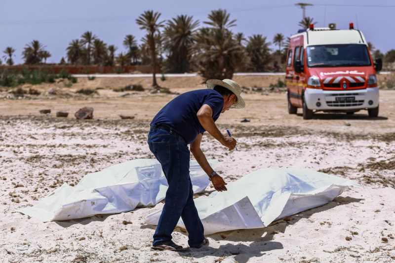 EDITORS NOTE: Graphic content / A representative of the Tunisian Red Crescent association checks bodies recovered from a boat carrying 86 migrants that capsized off the Tunisian coast while crossing the Mediterranean from Libya to Italy, as they lie on a beach in Aghir in Tunisia's southern island of Djerba on July 6, 2019. - The latest tragedy came to light the same week as 44 migrants were killed in an air strike on their detention centre in a suburb of the Libyan capital. (Photo by ANIS MILI / AFP)