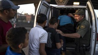 (FILES) In this file photo taken on May 16, 2019 migrants, mostly from Central America, board a van which will take them to a processing center in El Paso, Texas. - The Trump administration moved on July 15, 2019 to block most migrants who cross the US southern border after passing through Mexico from seeking asylum.A new rule redefining asylum eligibility -- to take effect on Tuesday -- is the latest attempt to stem the flow of undocumented migrants into the country, and comes amid White House frustration at Congress's failure to change asylum laws. (Photo by Paul Ratje / AFP)
