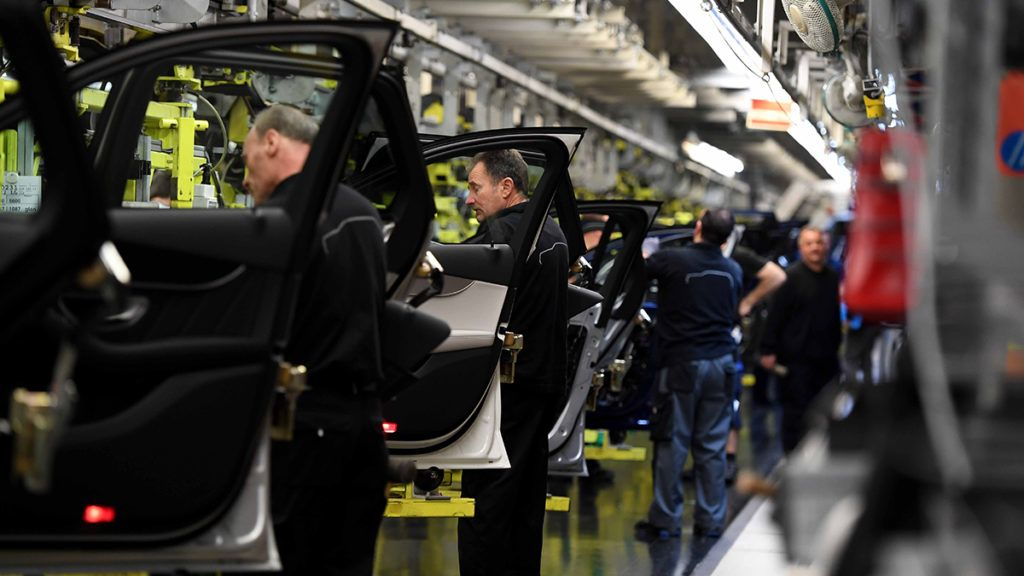 Employees work on an assembly line for Mercedes-Benz GLC sports utility vehicle (SUV) at the luxury automaker's factory in Bremen, Germany, on January 24, 2017. (Photo by PATRIK STOLLARZ / AFP)