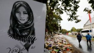People walk past flowers and tributes displayed in memory of the twin mosque massacre victims outside the Botanical Gardens in Christchurch on April 5, 2019. - The man accused of shooting dead 50 Muslim worshippers in a Christchurch mosque sat impassively April 5 as a New Zealand judge ordered him to undergo tests to determine if he is mentally fit to stand trial for murder. (Photo by Sanka VIDANAGAMA / AFP)