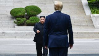 North Korea's leader Kim Jong Un walks to greet US President Donald Trump at the Military Demarcation Line that divides North and South Korea, in the Joint Security Area (JSA) of Panmunjom in the Demilitarized zone (DMZ) on June 30, 2019. (Photo by Brendan Smialowski / AFP)