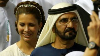 Mohammad bin Rashid al-Maktoum, Ruler of Dubai (R), arrives with his wife princess Haya Bint al-Hussein, to receive the golden trophy after his horse, African Story, won the Dubai World Cup, the world's richest horse race, at the Meydan race track in the Gulf Emirate on March 29, 2014. African Story swooped on front-running Mukhadram to win the 19th renewal of the $10 million Dubai World Cup, in the process breaking the track record with his winning time of 2min 01.61 sec. AFP PHOTO/MARWAN NAAMANI (Photo by MARWAN NAAMANI / AFP)