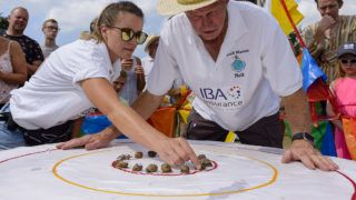 KING'S LYNN, ENGLAND - JULY 21: Kirstie Smith and Neil Riseborough prepare the snails racing in one of the knockout heats of the World Championship Snail Racing at Congham Village Fete on July 21, 2018 in King's Lynn, England. Over 100 snails have been taking part in the World Snail Racing Championships. Held in Congham near Kings Lynn, the championships which have been going for over 25 years form part of the village Fete to raise money for St Andrew's Church. (Photo by Mark Bullimore/Getty Images)