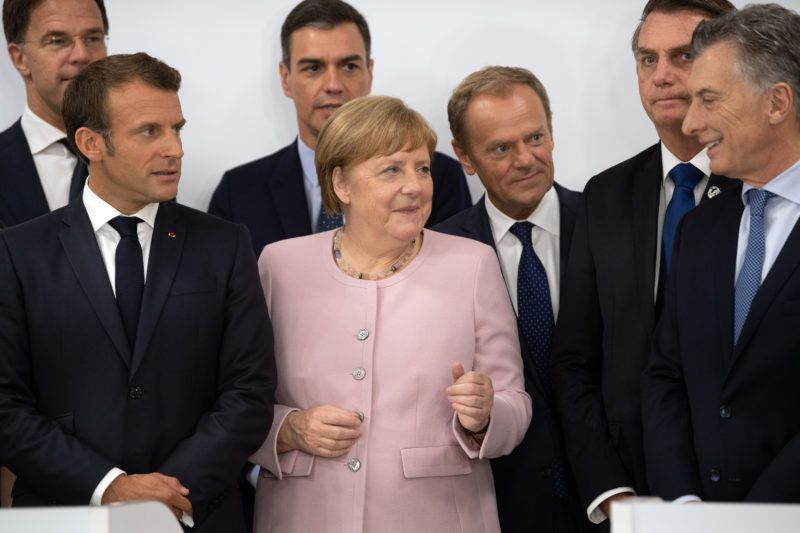 OSAKA, JAPAN - JUNE 29: Germany's Chancellor Angela Merkel and France's President Emmanuel Macron talk with Argentina's President, Mauricio Macri, during the announcement of a trade agreement between the European Union and Brazil, Argentina, Uruguay and Paraguay on June 29, 2019 in Osaka, Japan. World leaders have been meeting in Osaka for the annual Group of 20 summit to discuss economic, environmental and geopolitical issues. The US-China trade war has dominated the agenda with U.S President Trump and China's President Xi Jinping scheduled to meet on Saturday for an extended bilateral in an attempt to resolve the ongoing the trade war between the world's two largest economies. (Photo by Carl Court/Getty Images)