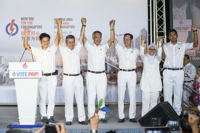 Lee Hsien Loong, Singapore's prime minister and leader of the People's Action Party (PAP), center, gestures with his team at an election results rally in Singapore on Saturday, Sept. 12, 2015. Singapore Prime Minister Lee Hsien Loong's People's Action Party won a majority of parliament seats, returning the party to power to continue more than five decades of rule. Photographer: Nicky Loh/Bloomberg via Getty Images