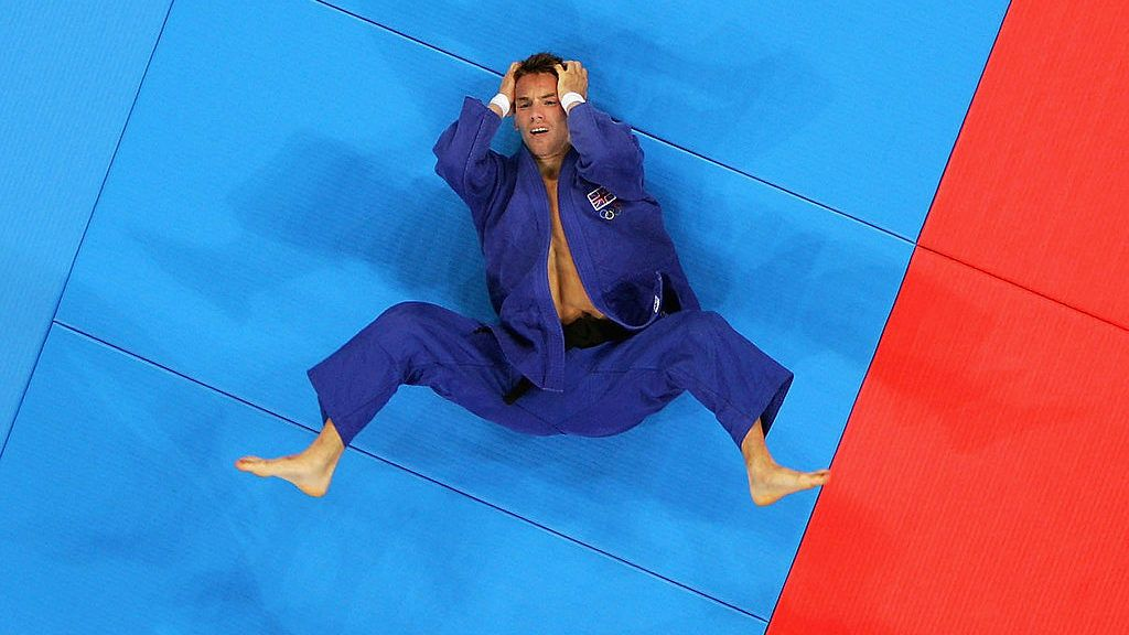 ATHENS - AUGUST 14:  Craig Fallon of Great Britain reacts to being defeated by Revazi Zintiridid of Greece in the men's judo -60 kg class preliminary repechages on August 14, 2004 during the Athens 2004 Summer Olympic Games at Ano Liossia Olympic Hall in Athens, Greece. (Photo by Scott Barbour/Getty Images)