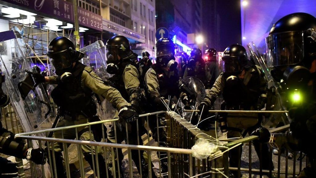 Riot police attempt to remove an improvised barricade created by protesters after a march against a controversial extradition bill in Hong Kong on July 21, 2019. - Hong Kong descended into chaos on the night of July 21 as riot police fired multiple volleys of tear at anti-government protesters, hours after China's office in the city was daubed with eggs and graffiti in a vivid rebuke to Beijing's rule. (Photo by Anthony WALLACE / AFP)