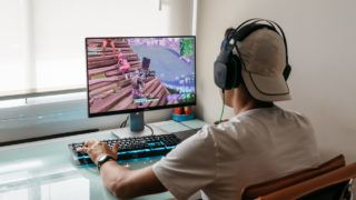 Madrid, Spain - August 15, 2018: Teenager playing Fortnite video game on PC. Fortnite is an online multiplayer video game developed by Epic Games