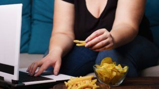 mindless snacking, overeating, lack of physical activity, laziness, homebody. . overweight woman engrossed in watching series at laptop eating fast food