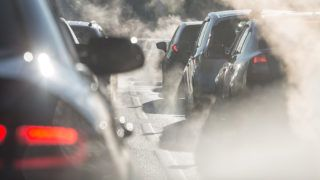 Moscow, Russia - August 08, 2017: Traffic jam. Blurred silhouettes of cars surrounded by steam from the exhaust pipes. Environmental pollution