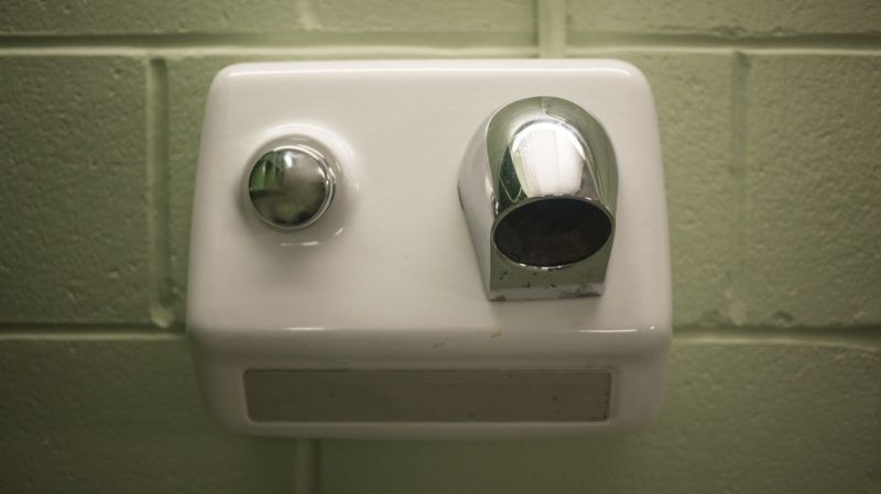 Old white and chrome electric hand dryer on a concrete wall in a school changing room.