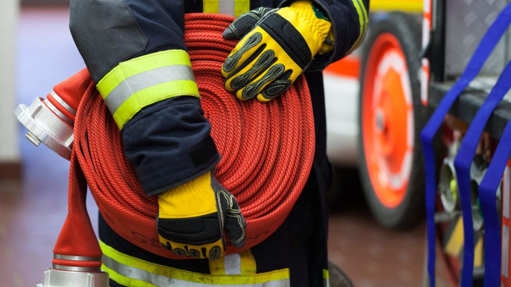 Firefighter wearing a rolled fire hose