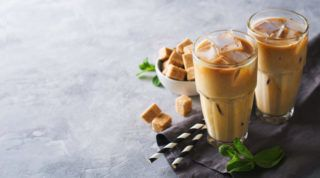 Iced coffee in tall glasses with cream and pieces of sugar, mint and straw over grey texture, copy space