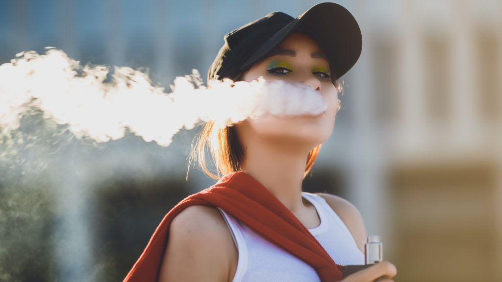 Pretty young asian girl vape popular ecig gadget,vaping device.Happy brunette vaper girl with e-cig.Portrait of smoker female model with electronic cigarette vaporizer.Ejuice vaping with fruit flavor liquid
