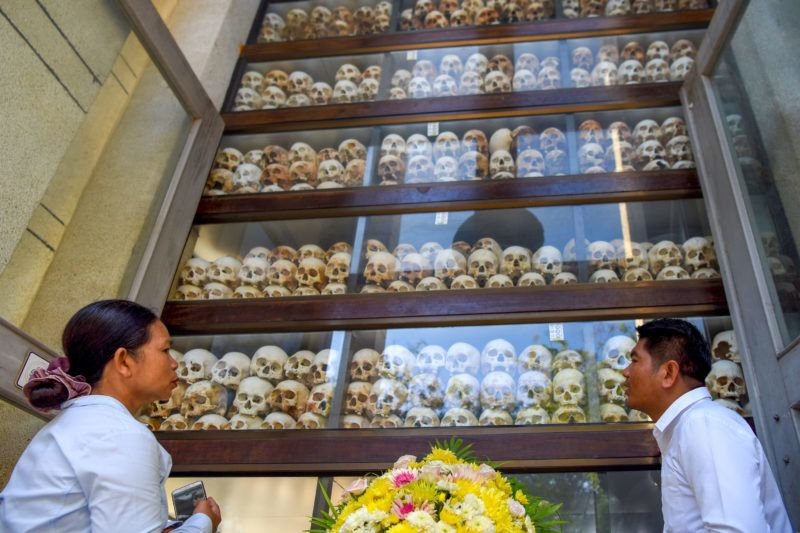 People look at skulls displayed in a stupa during the annual 'Day of Remembrance' at the Choeung Ek killing fields memorial in Phnom Penh on May 20, 2019. - Cambodians observed the annual 'Day of Remembrance' against the Khmer Rouge regime that ruled the country from 1975-79. (Photo by TANG CHHIN Sothy / AFP)