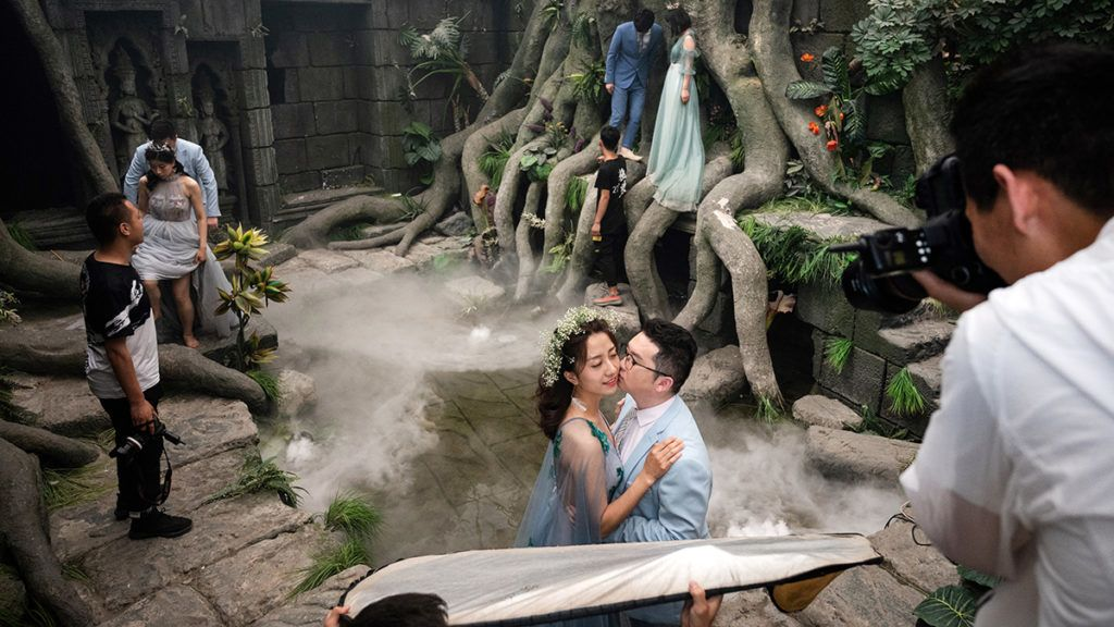 This picture taken on June 11, 2019 shows couples pose for pictures on an Angkor-Wat themed set for their pre-wedding photo shoot at the Love Story in Rome Studio in Beijing. - Increasingly elaborate pre-wedding photos are a booming industry in China, as young couples spend time and cash lining up glamorous photo shoots to display on their big day. (Photo by Fred DUFOUR / AFP)