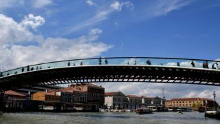 A photo taken on April 15, 2016 shows people walking across the Constitution Bridge (Ponte della Costituzione) which spans the Grand Canal in  Venice. AFP PHOTO / TIZIANA FABI - The bridge, designed by Santiago Calatrava, was installed and opened to the public in 2008. (Photo by TIZIANA FABI / AFP)