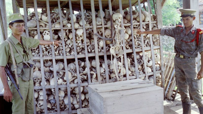 Cambodian soldiers point to skeletons of about 3 000 victims of the genocide perpetrated by the Khmer Rouge during their 1975-78 reign in Cambodia, on September 20, 1991, in Sisophon (or Serei Saophoan or Serei Sophon). The remains are kept in a Buddhist temple as a memorial to the victims. (Photo by STEFAN ELLIS / AFP)