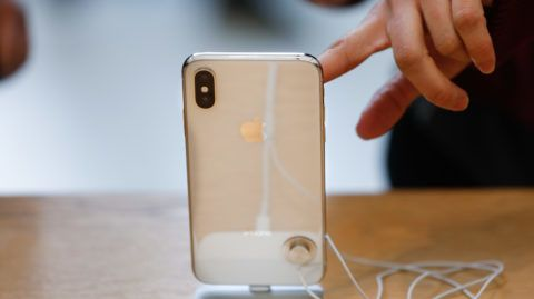 A customer touches the screen of the new iPhone X at the Apple Store Union Square on November 3, 2017, in San Francisco, California. - Apple's flagship iPhone X hits stores around the world as the company predicts bumper sales despite the handset's eye-watering price tag, and celebrates a surge in profits. (Photo by Elijah Nouvelage / AFP)