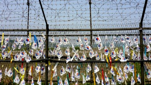 """15 May 2019, South Korea, Paju: South Korean flags described with wishes hang from a barbed wire fence on the South Korean side of the """"common security zone"""" on the border with North Korea in the Demilitarized Zone (DMZ). Photo: Peter Gercke/dpa-Zentralbild/ZB"""