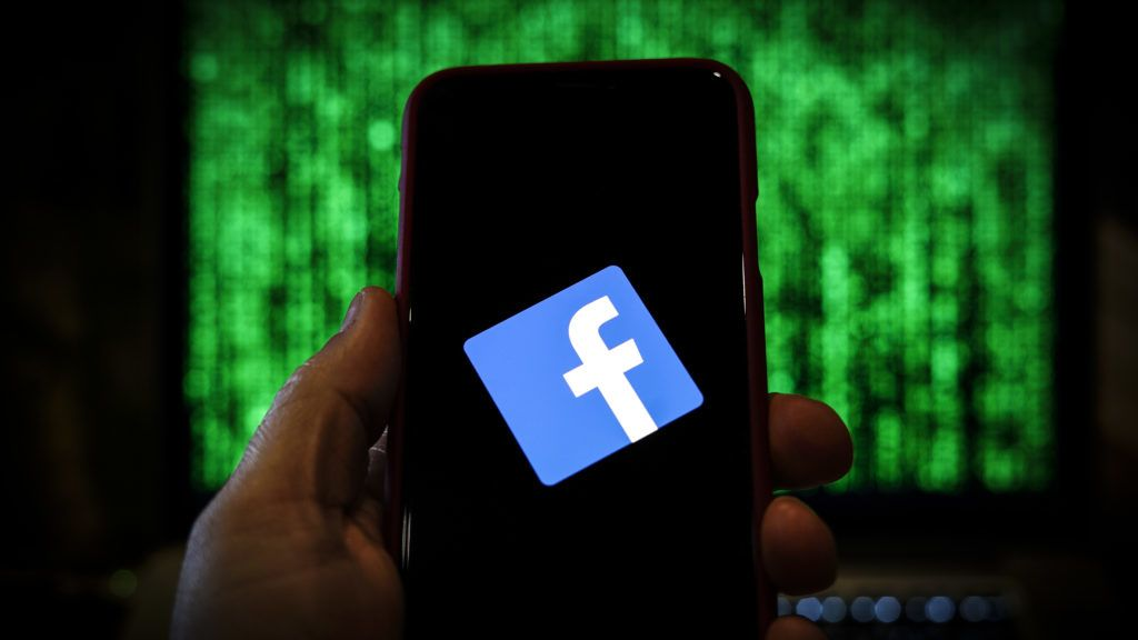 The Facebook logo is seen displayed on a mobile device in front of a screen with data in this photo illustration in Warsaw, Poland on March 19, 2019. (Photo by Jaap Arriens/NurPhoto)