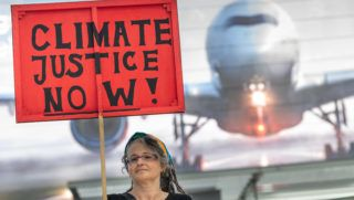 """A woman holds up a poster reading """"Climate Justice Now!"""" during a demonstration for climate protection and against travelling by airplane on July 26, 2019 at the airport in Munich, southern Germany, as school holidays started in the southern state of Bavaria. (Photo by Peter Kneffel / dpa / AFP) / Germany OUT"""