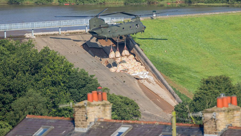Personnel use a Royal Air Force (RAF) Chinook helicopter to lower bags of aggregate to reinforce the damaged spillway of the Toddbrook Reservoir dam above the town of Whaley Bridge in northern England on August 2, 2019. - Emergency services continued work to repair a damaged dam they fear could collapse as hundreds of evacuated residents of the northern town of Whaley Bridge spent the night away from home. (Photo by Roland HARRISON / AFP)