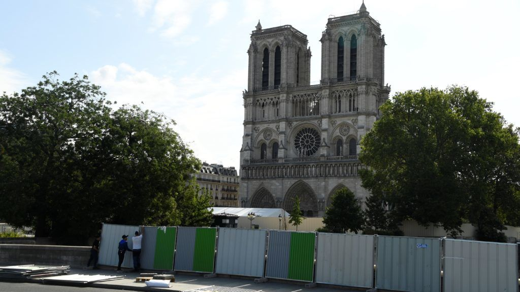 Workers install pallissades in front Notre-Dame cathedral in Paris before a decontamination work on August 13, 2019. - The area around Notre-Dame Cathedral in Paris was sealed off early on Tuesday as workers prepared to apply a special gel to absorb lead particles that seeped into the soil in the wake of the April 15 blaze. (Photo by BERTRAND GUAY / AFP)