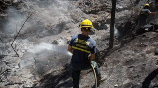 A firefighter douses an area affected by wildfires in Gran Canaria on the Spanish Canary Islands on August 13, 2019. - Firefighters have managed to contain a fire raging on the Spanish holiday island of Gran Canaria which sparked the evacuation of hundreds of people, local officials said. (Photo by DESIREE MARTIN / AFP)